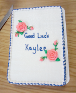 [photo of a cake; lettering on cake reads Good Luck Kaylee]