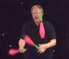 [photo of a man juggling a set of four juggling pins]