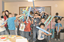 [photo of a group of kids playing light sabers with foam noodles]
